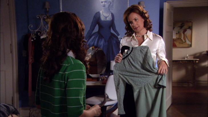 Madre enseñándole un vestido a su hija