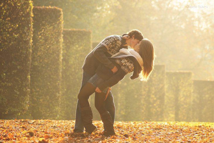 Pareja besándose sobre unas hojas de árbol secas