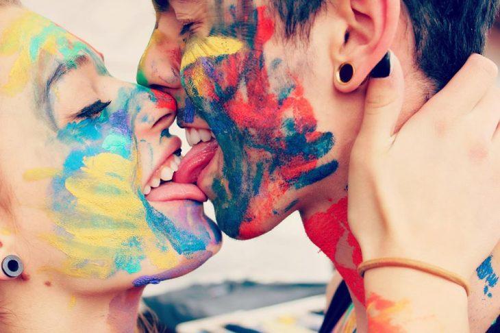 Pareja de novios besándose con la cara llena de pintura