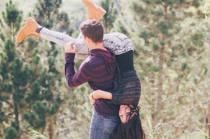 Chico cargando a su novia en el hombro