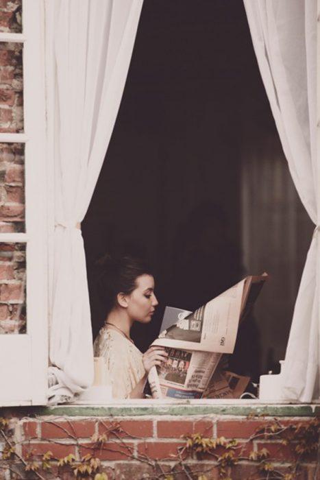 chica leyendo el periódico en una ventana