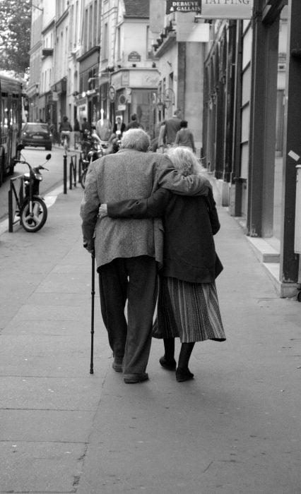 Pareja de abuelitos abrazados caminando por la calle
