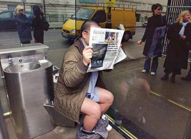 hombre leyendo un periódico sentado en un baño