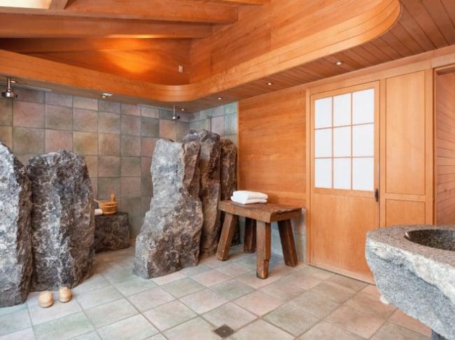 baño con diseños en piedra y paredes de madera