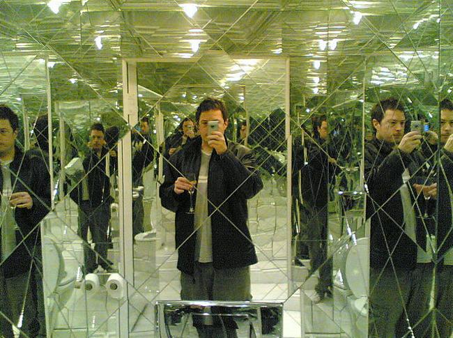 hombre tomandose una foto en un baño que esta hecho de espejos