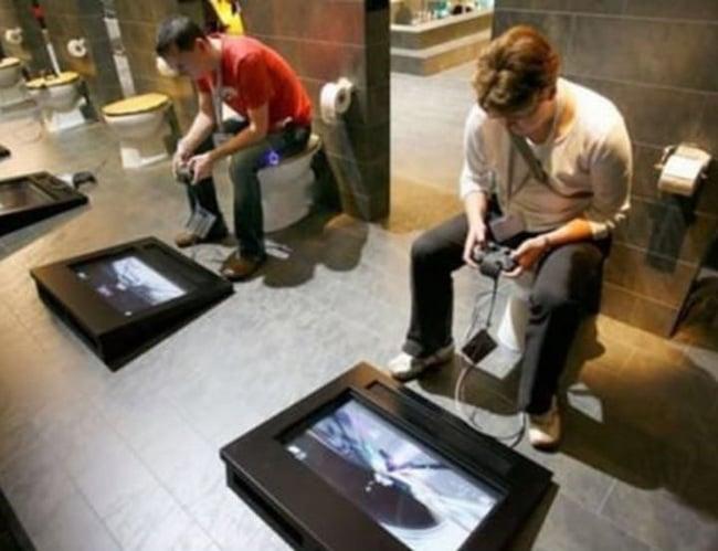hombres sentados en la taza del baño y en el suelo una pantalla con controles para jugar vídeo juegos