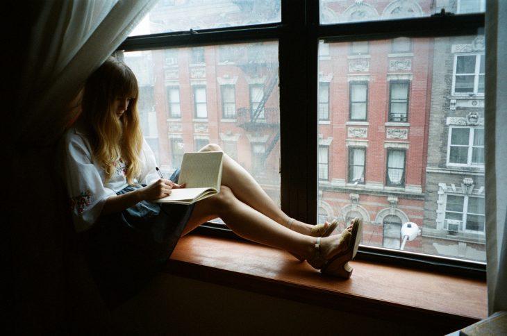Chica en una ventana escribiendo una carta