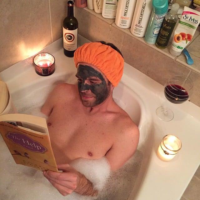 hombre tomando un baño en una tina con velas aromáticas y un libro