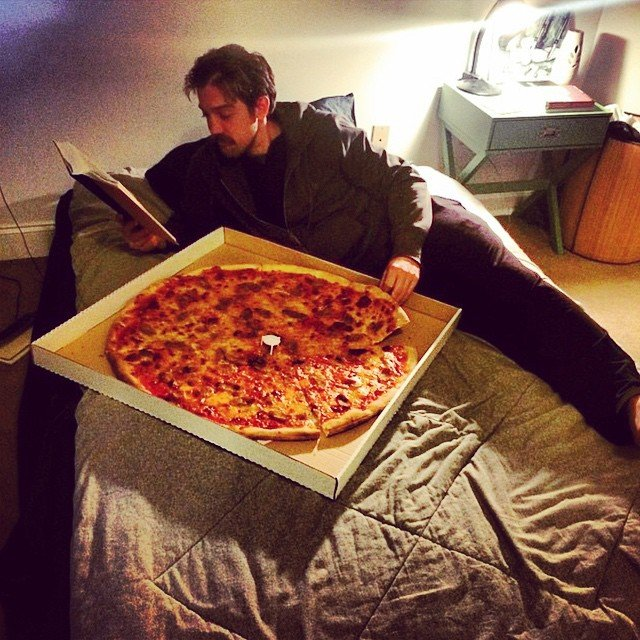 man eating pizza in bed