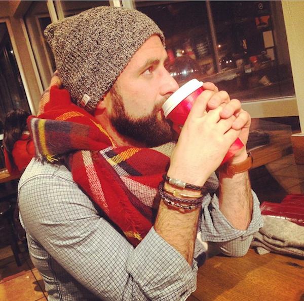 hombre ocn bufanda y gorro tomando un café