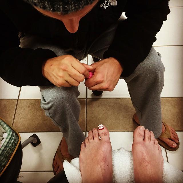 hombre pintándole las uñas a otro