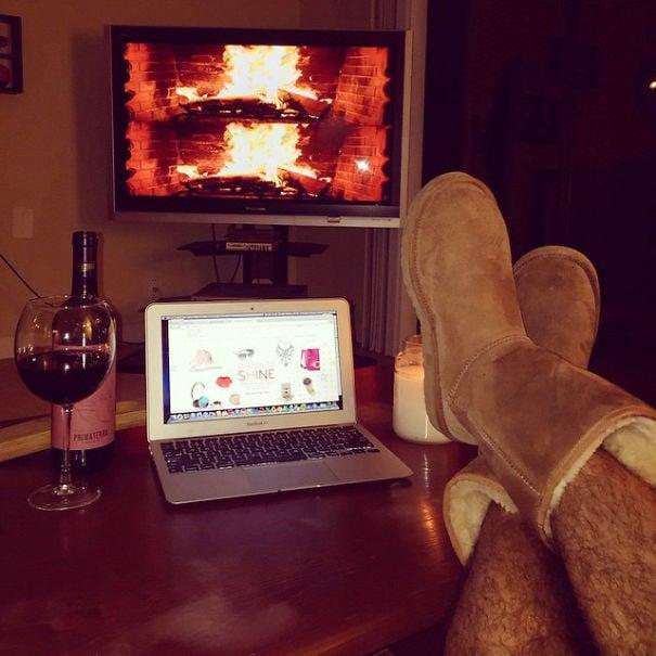 hombre con las piernas sobre una mesa viendo su computadora y tomando una copa de vino