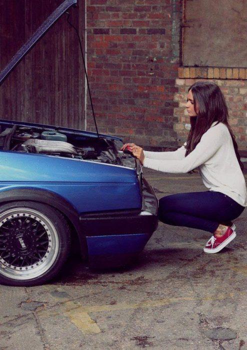 Chica tratando de arreglar un carro