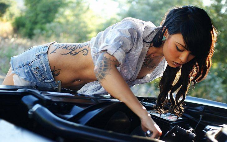 Chica con tatuajes arreglando un carro