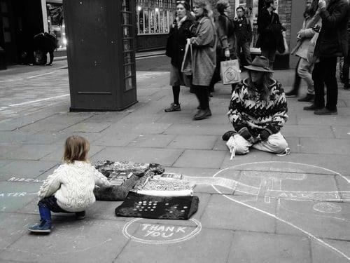 niña entregándole dinero a un hombre sin hogar