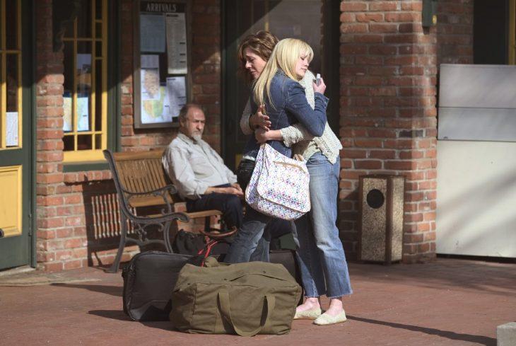 mujer abrazando a una joven en la estación de trenes