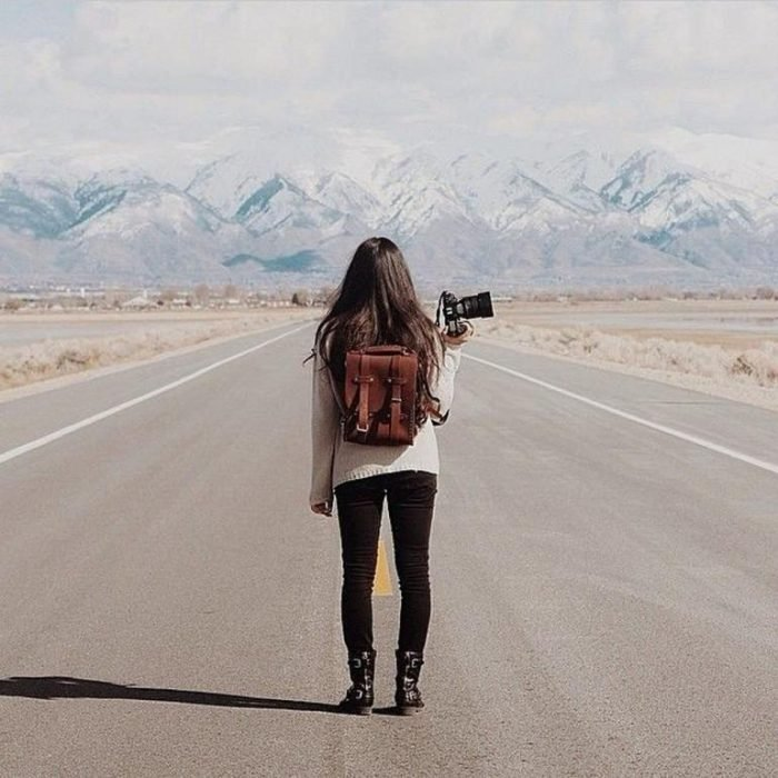 mujer con una cámara en medio de la carretera