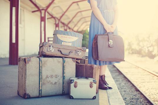 mujer a un lado de las vías del tren esperando con sus maletas