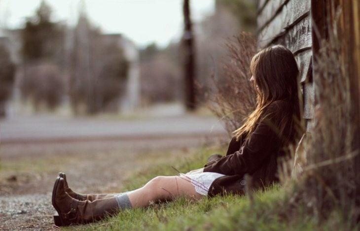 mujer sentada sola en el pasto recargando su espalda en una pared