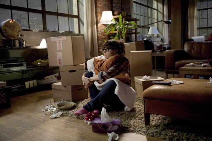 mujer sentada en el suelo rodeada de cajas y platos de comida