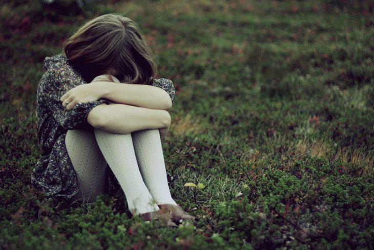 mujer sentada en el pasto abrazando sus rodillas y llorando