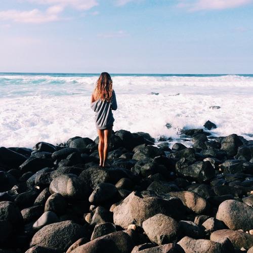 chica parada en unas rocas admirando el mar