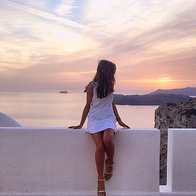 chica recargada en una pared viendo el amanecer