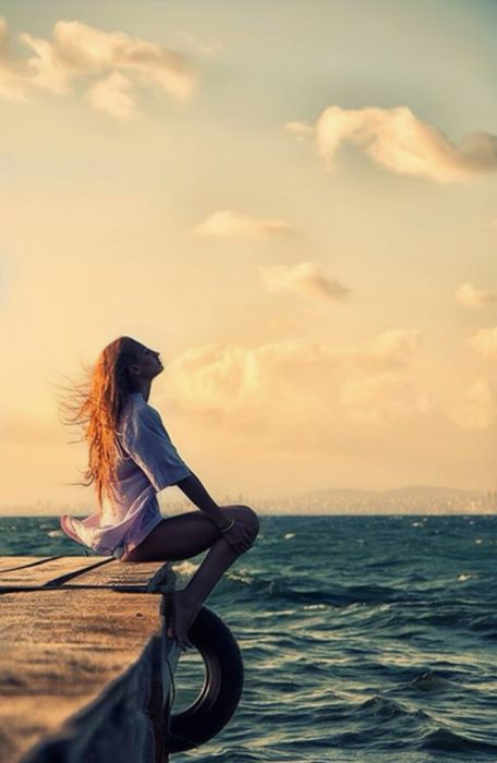 chica sentada en un muelle sintiendo el viento en su cara