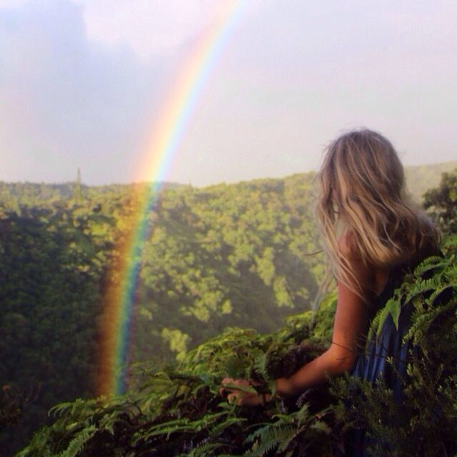 chica sentada en la selva observando un arcoiris