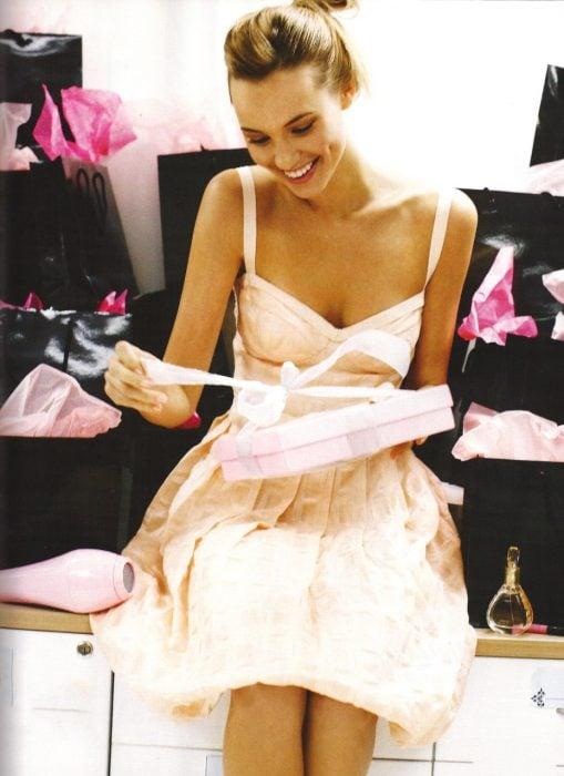 chica sentada abriendo un regalo