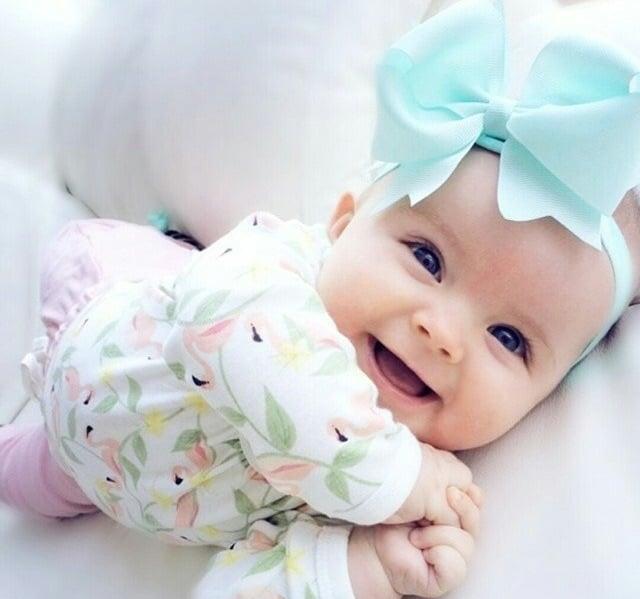 bebe sonriendo recostada en una cama y usando un moño de color azul en la cabeza