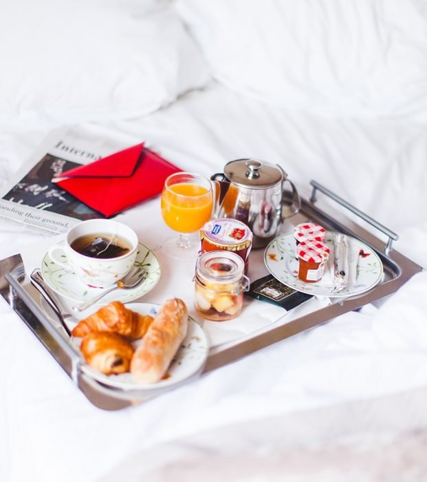 desayuno continental sobre la cama y una cartade amor