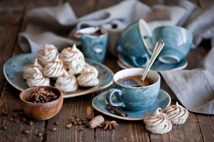 el olor del cafe en una taza de ceramica azul con panecillos