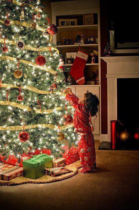 niña en pijama arreglando el pino de navidad