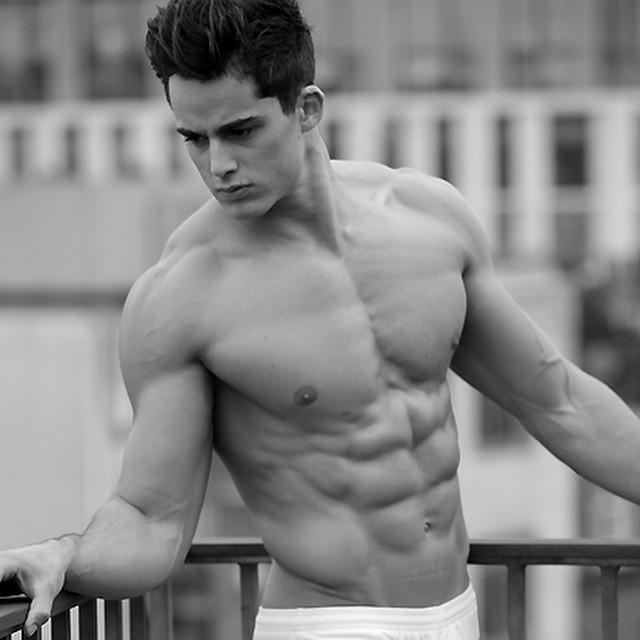 hombre recargado en una valla mostrando sus abdominales