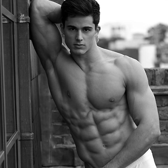 hombre recargado en la pared enseñando sus músculos