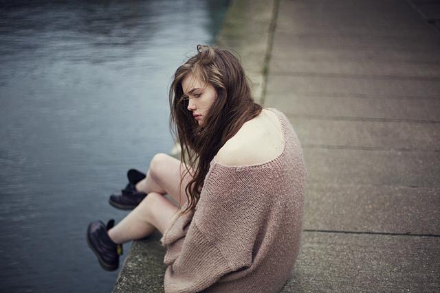 mujer sentada en un muelle con los pies colgando