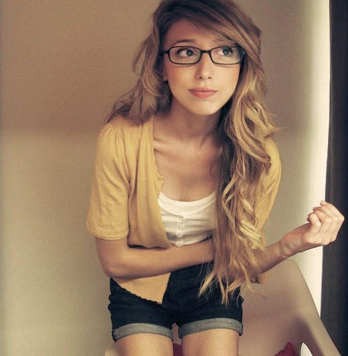 chica recargada en la pared usando lentes