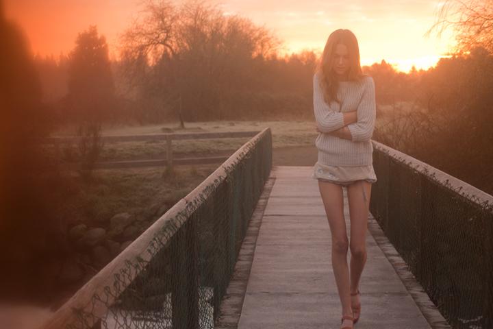 mujer caminando sobre un puente abrazándose a si misma