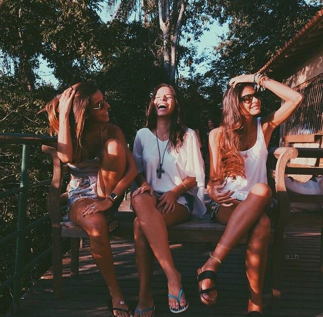 hermanas sentadas en el parque platicando u bromeando en shorts