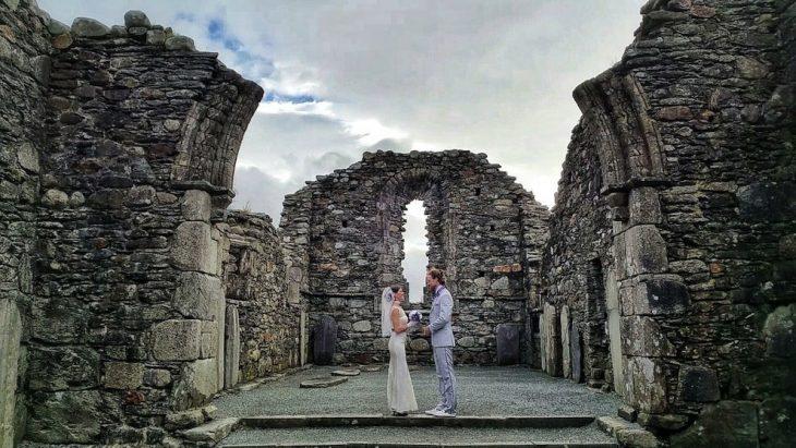 pareja parada frente a las ruinas de una antigua catedral en irlanda, vestidos para la ceremonia de su boda
