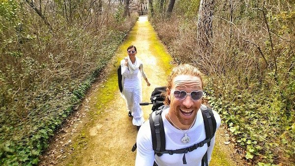pareja de viajeros caminando con mochilas en sus espaldas por el camino de una selva