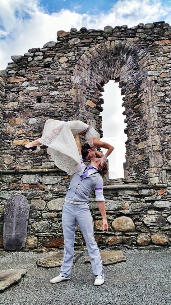 pareja haciendo acrobacias frente a las ruinas de una antigua catedral