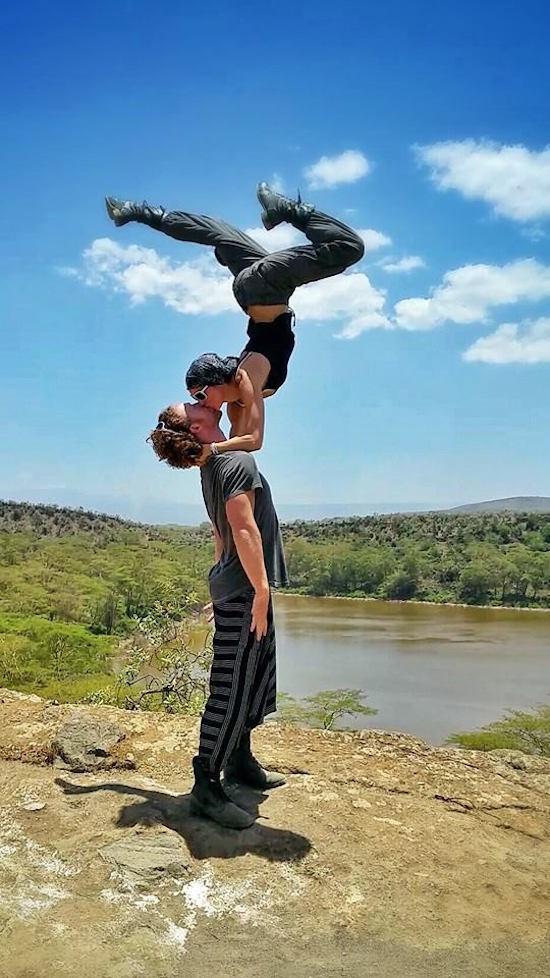 pareja haciendo acrobacias para besarse frente a un lago