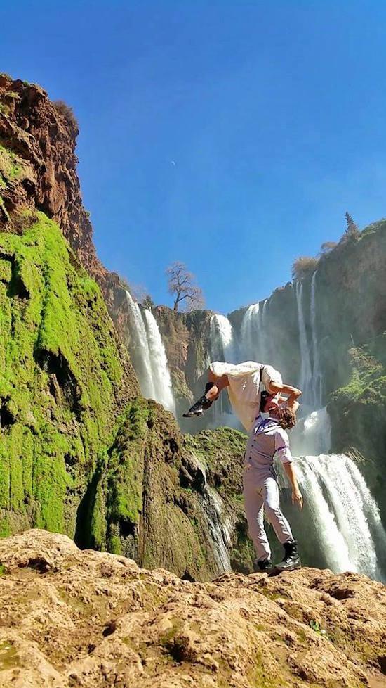 novio sosteniendo a la novia en brazos mientras están parados en una roca frente a las cascadas de marruecos