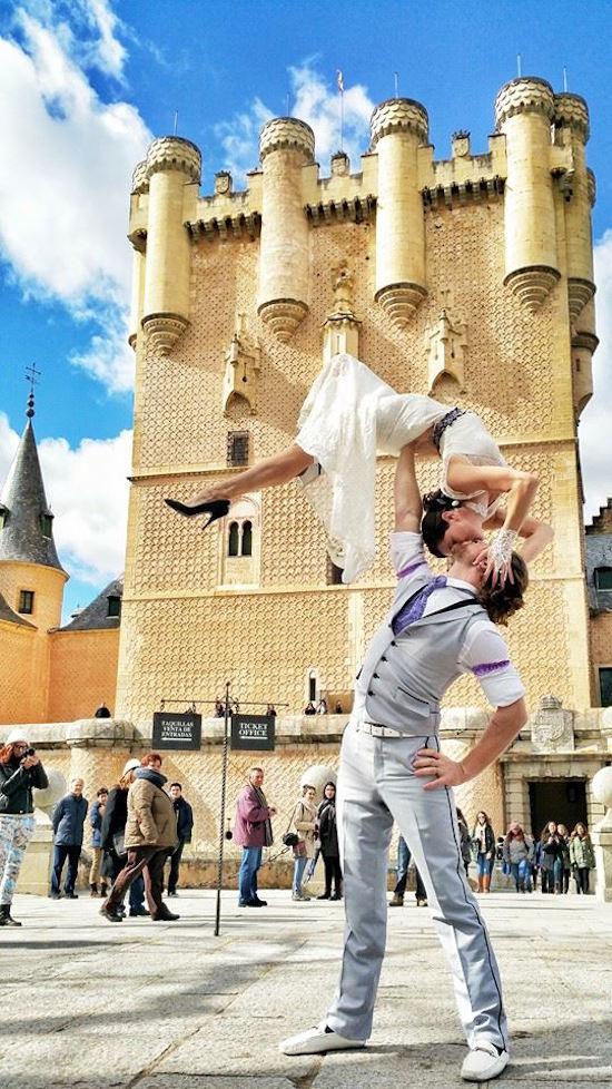 pareja haciendo acrobacias en una plaza de Segovia, España vestidos de novios