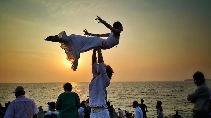 novio cargando a la novia frente a la playa mientras aparece el atardecer