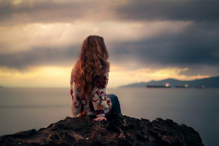 Chica sentada en una piedra viendo al mar