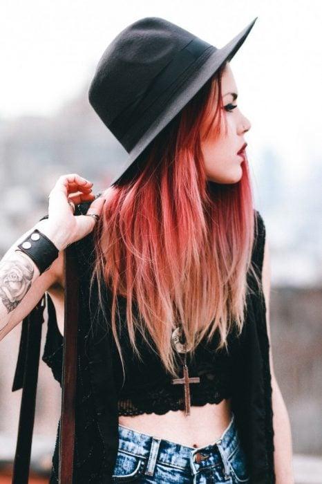 Chica de cabello rojo con tatuajes y perforaciones