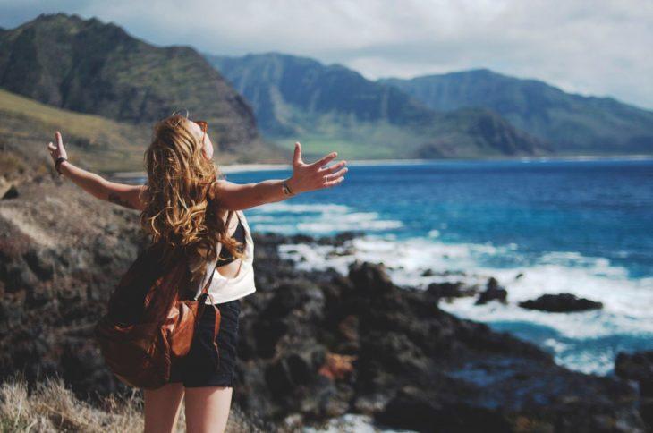Chica al filo de la montaña con vista al mar y los brazos abiertos